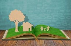 Papierschnitt des Familiensymbols auf Buch Stockbild