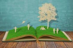 Papierschnitt des Kindspiels auf altem Buch stockbilder