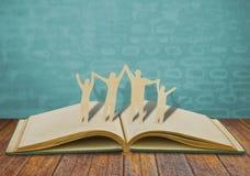 Papierschnitt-Familiensymbol auf altem Buch Stockfotografie