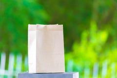 Papiertüte auf dem Holz und Baum undeutlichen bokeh Hintergrund im Garten Unter Verwendung der Tapete für Paketarbeitsfoto Lizenzfreies Stockfoto