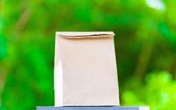 Papiertüte auf dem Holz und Baum undeutlichen bokeh Hintergrund im Garten Unter Verwendung der Tapete für Paketarbeitsfoto Stockfotos