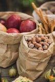 Papiertüten hergestellt von Kraftpapier mit nuts Haselnuss, roten Äpfeln und Brot auf einem Holztisch Stockfotografie