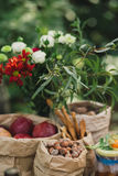 Papiertüten mit Nüssen, Haselnüssen, roten Äpfeln und einem grünen Blumenstrauß Stockfotos