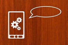 Papiertablette oder Smartphone mit Zahnrädern und Rede sprudeln, copyspace Stockbild