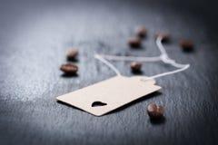 Papiertag mit Herzen auf einem dunklen Steinhintergrund mit Kaffee auf einem Hintergrund Lizenzfreie Stockbilder