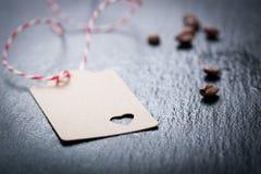 Papiertag mit Herzen auf einem dunklen Steinhintergrund mit Kaffee auf einem Hintergrund Stockfoto