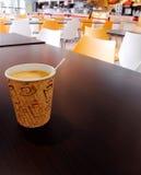 PapierTasse Kaffee auf die Cafeteriatabellenoberseite Stockfotografie