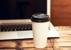 Papiertasse kaffee auf hölzernem Schreibtisch und Laptop Lizenzfreie Stockfotografie
