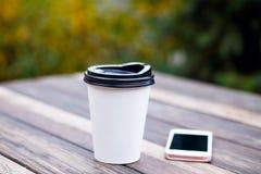 Papiertasse kaffee und Handy im Café Stockfotografie