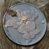 Papillon en bois tacheté sur la plaque de fleur en métal Images stock