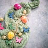 Papillons colorés en bois avec des oeufs de pâques Images stock