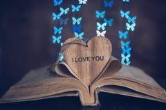 Papillons en bois de bokeh de livre de coeur Photo stock