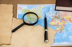 Papiro em um mapa do mundo, em uma pena e em uma lente de aumento imagem de stock