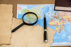 Papiro su una mappa, su una penna e su una lente di mondo immagine stock