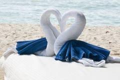 Papiroflexia de la toalla de cisnes en una forma del corazón en un balneario de la playa Foto de archivo libre de regalías