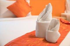 Papiroflexia de la toalla preparada en una cama Fotografía de archivo