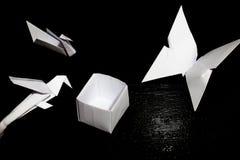 Papiroflexia que dobla el papel, la grúa de papel, el loro, la mariposa y una caja Imagen de archivo libre de regalías
