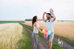 Pappa, mamma och barn som har roligt utomhus arkivbild