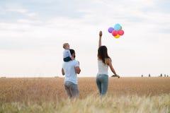 Pappa, mamma och barn som har roligt utomhus fotografering för bildbyråer