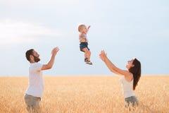 Pappa, mamma och barn som har roligt utomhus arkivfoto