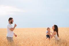 Pappa, mamma och barn som har roligt utomhus arkivbilder