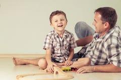 Pappa med pysen som spelar med leksakdrevet på golvet på Royaltyfria Foton