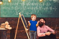 Pappa och unge som har gyckel, medan lära ny expertis Le läraren och den förvånade skolpojken i klassrum lycklig unge arkivfoto