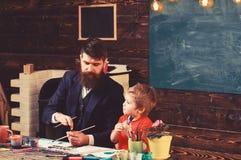 Pappa- och ungem?lningnatur Fader och son p? konstterapikursen royaltyfri foto