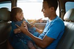 Pappa som killar hennes liten flicka i bilen arkivbilder