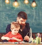 Pappa som undervisar hans son hur man målar Gullig unge som håller ögonen på hans fadermålning arkivfoto