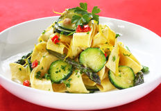 Pappardelle. Fresh pappardelle with zucchini, asparagus, peppers, and a creamy sauce.  Delicious wide ribbon pasta, garnished with parsley and lemon zest Stock Images