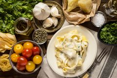 Pappardelle Pasta with Creamy Alfredo Sauce. Fine Pappardelle Pasta with White Creamy Alfredo Sauce on Dark Wooden Table Royalty Free Stock Image