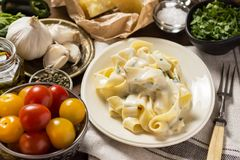 Pappardelle Pasta with Creamy Alfredo Sauce. Fine Pappardelle Pasta with White Creamy Alfredo Sauce on Dark Wooden Table Stock Images