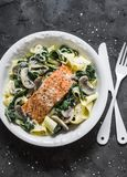 Pappardelle pasta with creamy spinach mushrooms sauce and baked salmon on a dark background, top view. Salmon florentine homemade. Pasta stock images