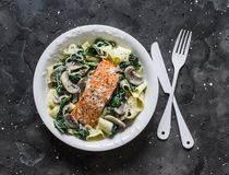 Pappardelle pasta with creamy spinach mushrooms sauce and baked salmon on a dark background, top view. Salmon florentine homemade. Pasta stock image