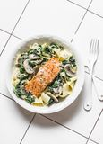Pappardelle pasta with creamy spinach mushrooms sauce and baked salmon on a light background, top view. Salmon florentine homemade. Pasta royalty free stock image