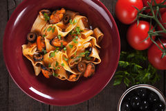 Pappardelle pasta with mussels and olives. Italian pappardelle pasta with mussels, olives and tomato sauce Royalty Free Stock Image