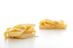 Pappardelle pasta på vit bakgrund Arkivfoton