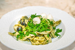 Pappardelle pasta with pesto. Concept of Italian cuisine Stock Photo