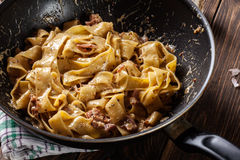 Pappardelle pasta with prosciutto and cheese sauce on pan Royalty Free Stock Photos