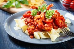 Pappardelle pasta with shrimp, tomatoes and herbs. Italian cuisine Royalty Free Stock Images