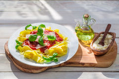 Pappardelle pasta with tomato sauce and basil in the sunny kitchen Royalty Free Stock Image