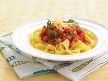 Pappardelle pasta with tomato sauce. Fresh pappardelle pasta with tomato sauce, chick peas, arugula and grated cheese in a white bowl on a knife and fork table Royalty Free Stock Images
