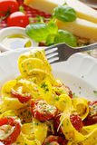 Pappardelle pasta with tomatoes and herbs on white plate Royalty Free Stock Image