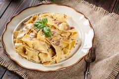 Pappardelle-Teigwaren mit Prosciutto- und Käsesoße auf einer Platte Lizenzfreie Stockfotos
