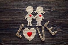 Pappe silhouettiert Mädchen und Jungen mit Herzen und der Wortliebe Lizenzfreie Stockbilder