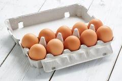 Pappeigestell mit Eiern auf weißer Tabelle Stockfotos