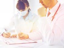Papper för doktors- och sjuksköterskahandstilrecept fotografering för bildbyråer