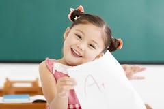 papper för liten flickavisningexamen med a-plus i klassrum fotografering för bildbyråer