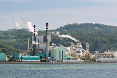 Papper maler fabriken nära en havsfjord royaltyfri bild